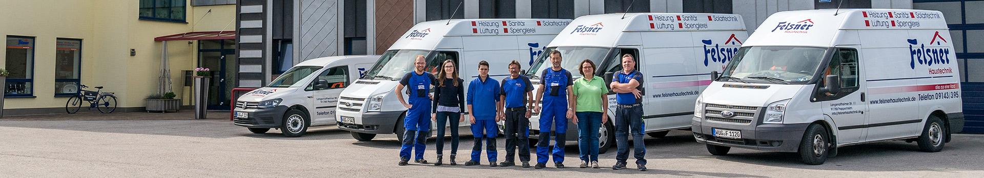 Felsner Team vor den Firmenwägen und dem Firmengebäude